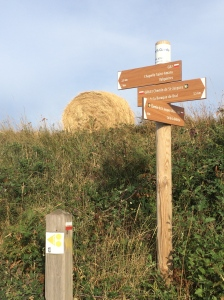 Which way? Hay bale behind signpost pointing in many directions