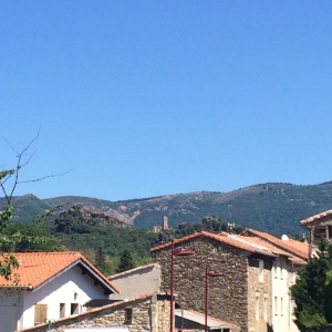 View over town rooftops to ancient ruin and mountains