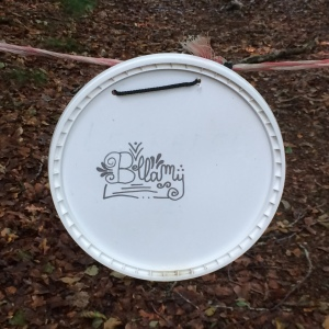 'Bellamy' on a large plastic lid handing on a string fence