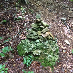 Mossy rock with stones piled into pyramid